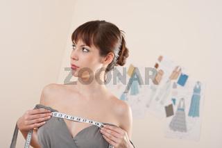 Fashion model trying gray dress in designer studio