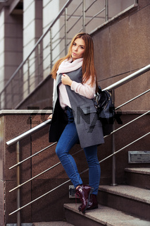 Young fashion woman in grey coat with handbag standing on the steps