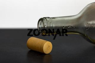 Empty opened wine bottle lies on the floor