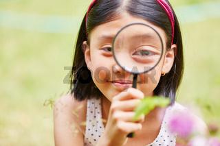 Mädchen als Forscherin mit Lupe