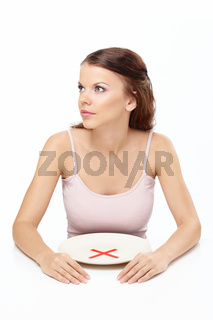 Attractive girl sits before empty plate with an interdiction sign