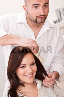 Professional hairdresser comb customer at salon