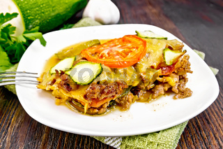 Casserole from minced meat and zucchini in plate on dark board