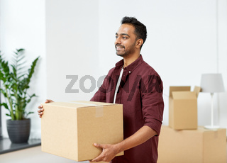 happy man with box moving to new home