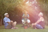 Seniors relaxing with Cannabis plant outdoors