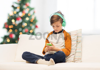 boy with smartphone and headphones at christmas