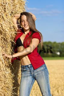 Junge Frau mit offener Bluse an Stroh gelehnt.