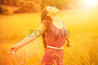 Summer Fun. Young happy woman enjoying golden sunlight on the wheat meadow