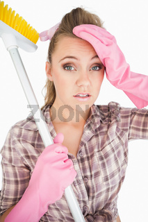 Portrait of tired young woman holding broom