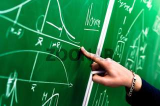 Hand of a student pointing at green chalk board