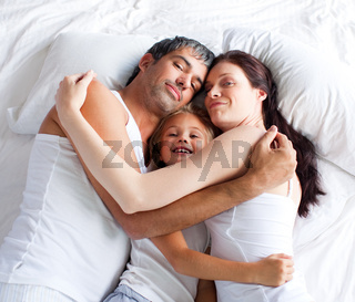Little gril relaxing on bed with her parents