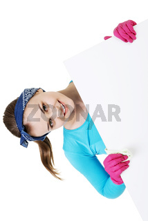 Happy cleaning woman showing blank sign board.