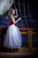 Beautiful girl in a white dress on a deck of the s