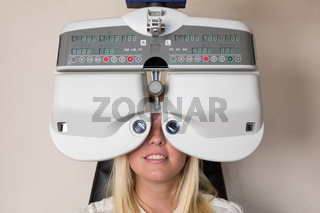 Patient eines Augenoptikers schaut durch Phoropter