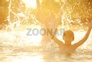 Happy children together splashing water