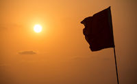 Silhouette of flag in sunset