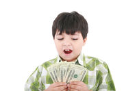 A smiling little boy is counting money
