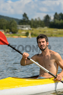Smiling sporty man kayaking on lake