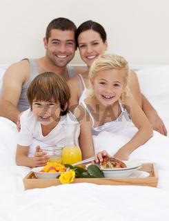Family having breakfast in bedroom