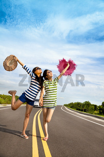 two girls having fun on the road trip at summertime