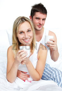 Couple drinking coffee in bed and smiling at the camera