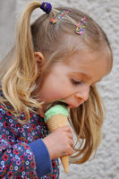 Cute little blond girl eating ice cream