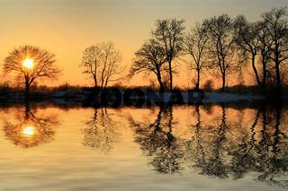 Beautiful reflection in the pond during the winter sunset