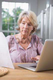 Focused mature woman using her laptop