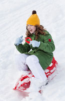 Girl rides sledge down hill