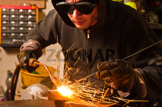worker welding with hot flame and sparks