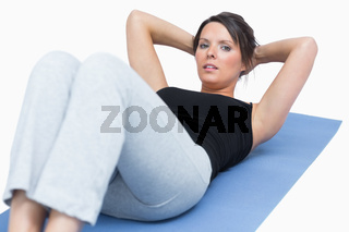 Portrait of woman doing situps on exercise mat over