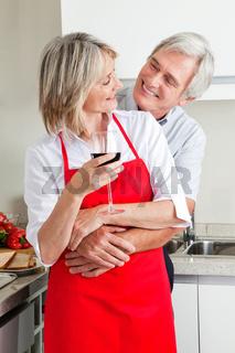 Senioren in Küche mit Wein