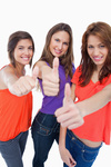 Three teenage girls proudly showing their happiness by putting their thumbs up