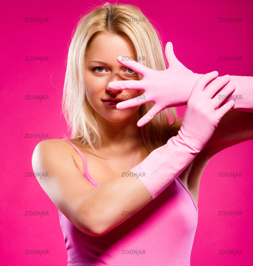 Woman wearing rubber gloves posing over pink background
