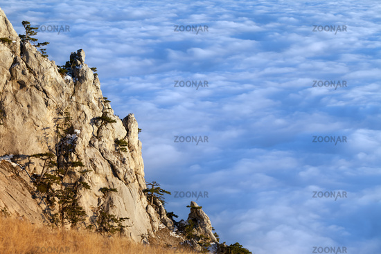 Sunlit cliffs and sea in clouds