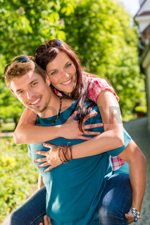 Happy couple woman jump on man's back