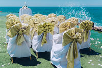 Row of wedding white chairs decorated with golden bows on the beach