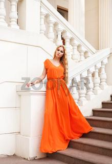 Beautiful blond woman in orange dress outdoors