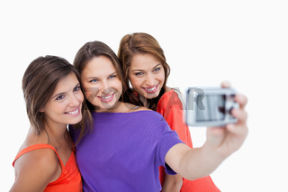 Three beautiful teenage girls standing side by side while being photographed