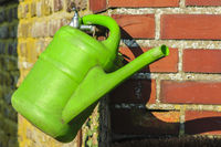 green watering can hanging on a red brick wall