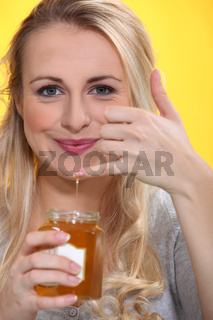 Smiling woman holding a honeypot