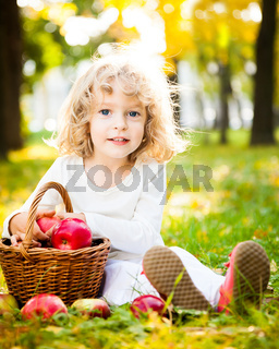 Child with basket of apples in autumn park