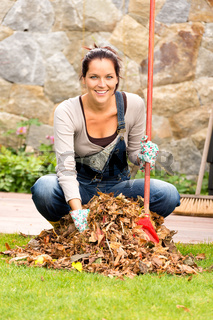 Cheerful woman sweeping leaves autumn pile backyard