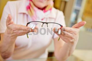 Hände beim Optiker bieten Brille an