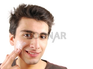 young handsome man applying face cream (over white background)