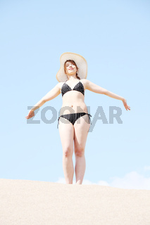 Young woman standing on beach in bikini and straw hat.