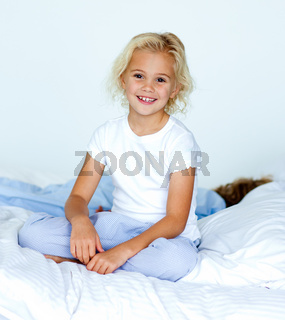 Little girl in bed smiling at the camera while her brother is sleeping