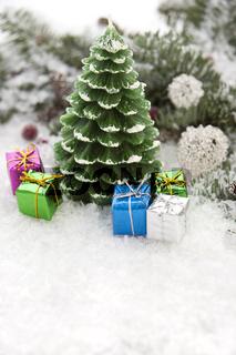 Weihnachtskerze im Schnee mit Geschenkpaketen