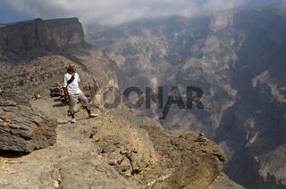 Wanderer steht auf einem Felsvorsprung in der Westflanke des Grand Canyon von Oman und schaut ins Wadi an Nakhar