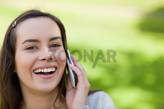 Young laughing woman showing her happiness while talking on the phone